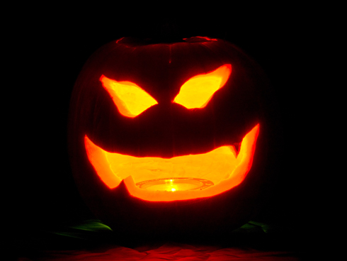carved scary pumpkin face with candle for halloween
